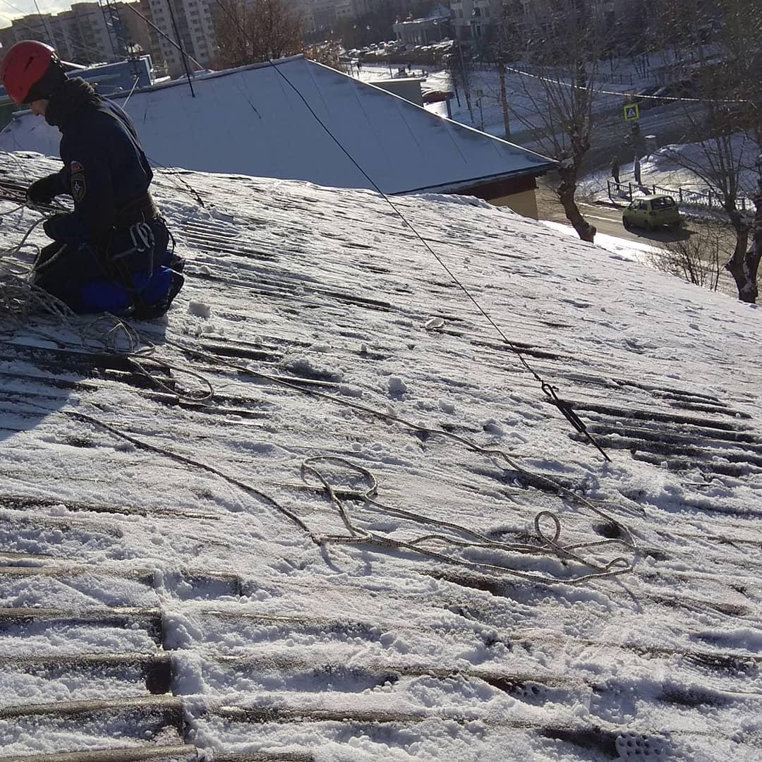 Чистка снега и льда с наклонных металлических крыш жилых домов